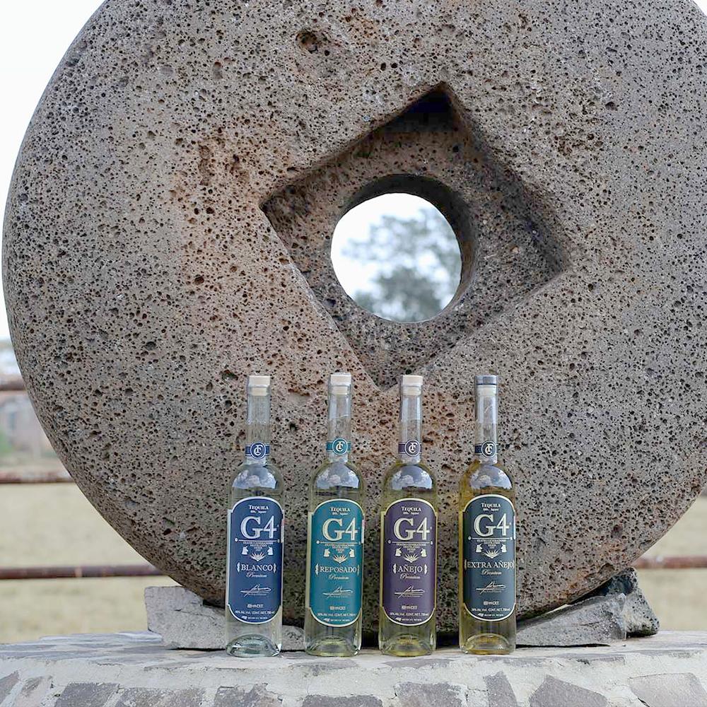 Das aktuelle Produkt Line-Up von G4 Tequila - vor der alten Stein-Tahona. Blanco, Reposado, Anejo und Extra Anejo von G4 Tequila.
